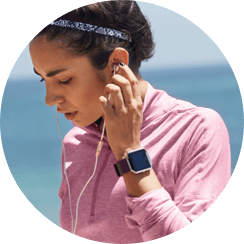 Photo of a women wearing earbuds and a Fitbit